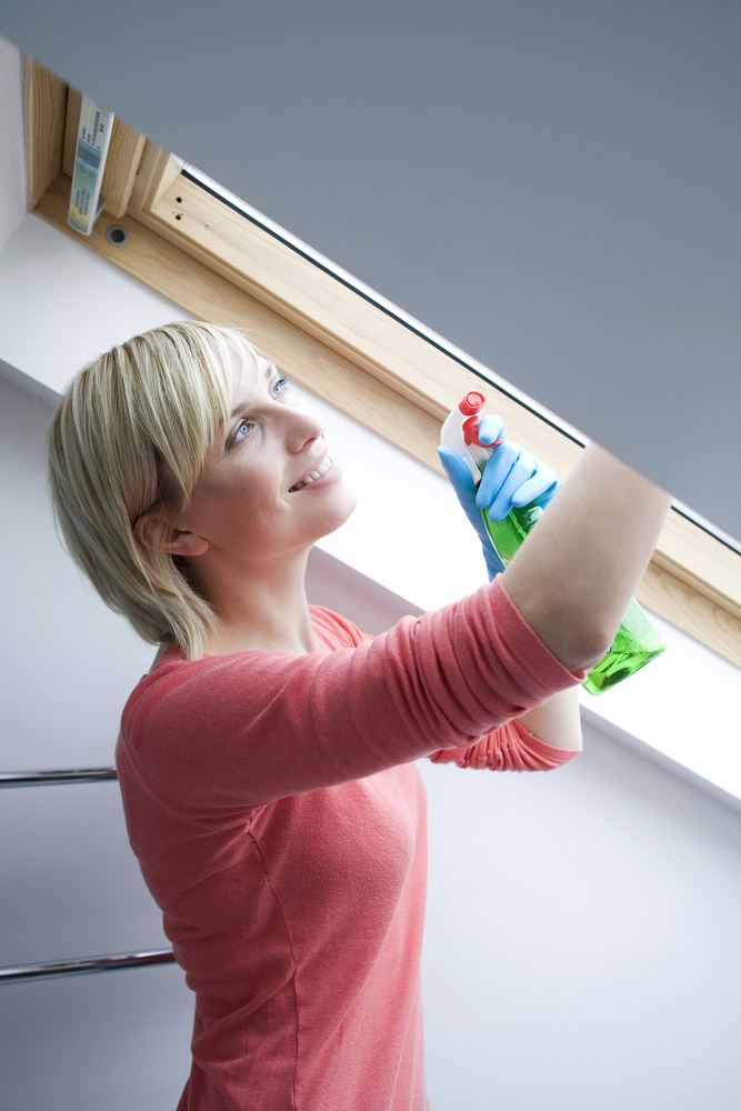 Attic Cleanup Tips: A woman cleaning an attic window